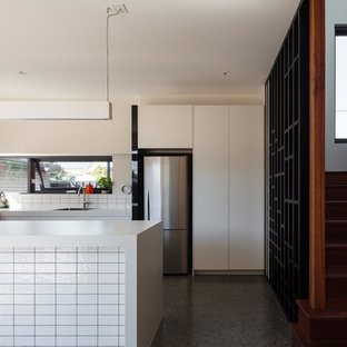 This is an example of a contemporary u-shaped kitchen in Melbourne with an undermount sink, flat-panel cabinets, white cabinets, white splashback, stainless steel appliances, concrete floors, a peninsula, grey floor and white benchtop.