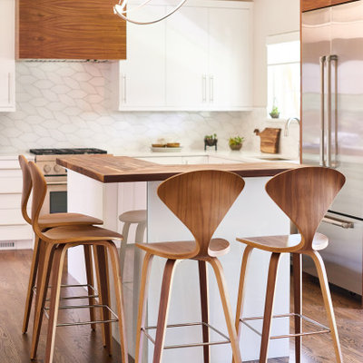 Example of a mid-sized trendy l-shaped medium tone wood floor and brown floor open concept kitchen design in Denver with an undermount sink, flat-panel cabinets, white cabinets, wood countertops, white backsplash, ceramic backsplash, stainless steel appliances, an island and brown countertops