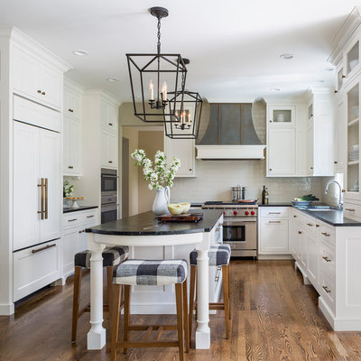 Mid-sized elegant medium tone wood floor and brown floor kitchen photo in Minneapolis with a single-bowl sink, recessed-panel cabinets, white cabinets, granite countertops, white backsplash, ceramic backsplash, stainless steel appliances, an island and black countertops