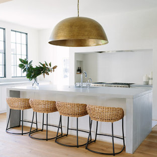Coastal kitchen remodeling - Beach style light wood floor and beige floor kitchen photo in Nashville with a single-bowl sink, flat-panel cabinets, white cabinets, white backsplash, stainless steel appliances, an island, gray countertops and concrete countertops