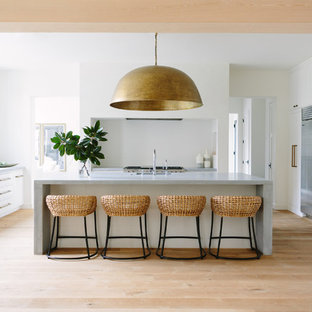 Large beach style eat-in kitchen photos - Inspiration for a large beach style u-shaped light wood floor and beige floor eat-in kitchen remodel in Nashville with flat-panel cabinets, white cabinets, concrete countertops, white backsplash, an island, an undermount sink and stainless steel appliances