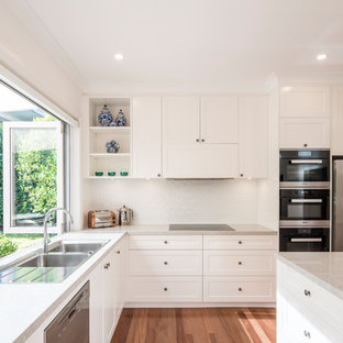 Design ideas for a large transitional l-shaped kitchen in Sydney with a drop-in sink, shaker cabinets, white cabinets, quartz benchtops, white splashback, porcelain splashback, medium hardwood floors, with island, stainless steel appliances, brown floor and grey benchtop.
