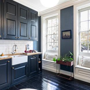 Foto på ett mellanstort vintage beige linjärt kök, med en rustik diskho, luckor med upphöjd panel, svarta skåp, träbänkskiva, vitt stänkskydd, stänkskydd i tunnelbanekakel, mörkt trägolv och svart golv