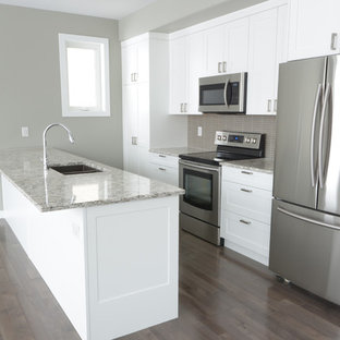 Small arts and crafts single-wall eat-in kitchen in Other with a double-bowl sink, shaker cabinets, white cabinets, granite benchtops, grey splashback, matchstick tile splashback, stainless steel appliances, light hardwood floors and with island.