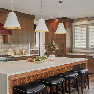 Large transitional open concept kitchen inspiration - Inspiration for a large transitional l-shaped dark wood floor open concept kitchen remodel in Grand Rapids with flat-panel cabinets, dark wood cabinets, granite countertops, brown backsplash, subway tile backsplash, stainless steel appliances, an island and an undermount sink
