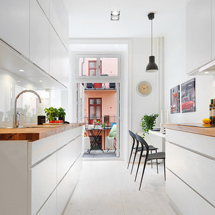 Mid-sized scandinavian eat-in kitchen inspiration - Eat-in kitchen - mid-sized scandinavian galley painted wood floor eat-in kitchen idea in Stockholm with flat-panel cabinets, white cabinets, wood countertops, white backsplash, glass sheet backsplash, no island and a drop-in sink