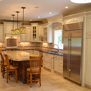 Medium sized classic l-shaped kitchen/diner in New York with a built-in sink, raised-panel cabinets, white cabinets, granite worktops, beige splashback, stone tiled splashback, stainless steel appliances, marble flooring and an island.