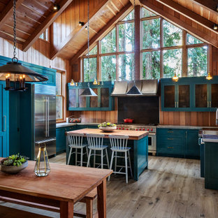This is an example of a large rustic u-shaped open plan kitchen in San Francisco with an integrated sink, shaker cabinets, blue cabinets, granite worktops, stainless steel appliances, medium hardwood flooring, an island, grey floors and grey worktops.