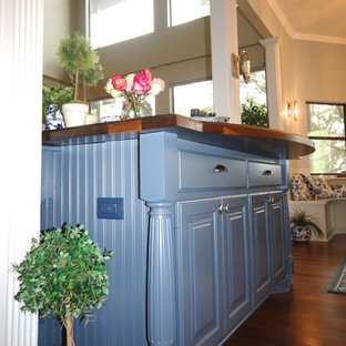Design ideas for a large victorian galley open plan kitchen in Austin with raised-panel cabinets, blue cabinets, wood benchtops, dark hardwood floors and multiple islands.