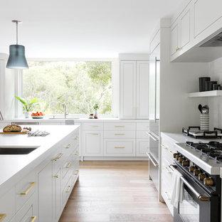 サンフランシスコの広いL型トランジショナルスタイルのキッチンの画像 (シングルシンク、グレーのキャビネット、クオーツストーンカウンター、白いキッチンパネル、セラミックタイルのキッチンパネル、黒い調理設備、淡色無垢フローリング、アイランドキッチン、グレーのキッチンカウンター、レイズドパネル扉のキャビネット、ベージュの床)