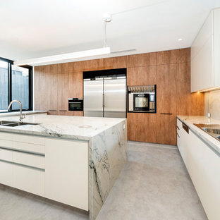 This is an example of a modern u-shaped kitchen in Melbourne with a drop-in sink, flat-panel cabinets, medium wood cabinets, stainless steel appliances, with island, grey floor and grey benchtop.
