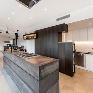 Contemporary u-shaped open plan kitchen in Perth with dark wood cabinets, concrete benchtops, white splashback, porcelain splashback, concrete floors, with island, grey floor, an undermount sink, flat-panel cabinets and stainless steel appliances.
