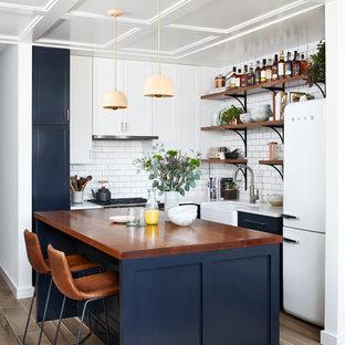 ワシントンD.C.の小さいエクレクティックスタイルのおしゃれなキッチン (エプロンフロントシンク、シェーカースタイル扉のキャビネット、青いキャビネット、クオーツストーンカウンター、白いキッチンパネル、セラミックタイルのキッチンパネル、白い調理設備、磁器タイルの床、茶色い床) の写真