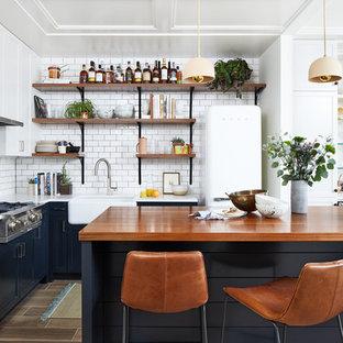 Idée de décoration pour une petit cuisine ouverte design en L avec un évier de ferme, un placard à porte shaker, des portes de placard bleues, un plan de travail en bois, une crédence blanche, une crédence en carreau de céramique, un sol en carrelage de porcelaine, un îlot central, un sol marron, un électroménager blanc et un plan de travail marron.