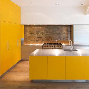 Foto på ett stort industriellt kök, med en integrerad diskho, släta luckor, gula skåp, bänkskiva i rostfritt stål, flerfärgad stänkskydd, stänkskydd i glaskakel, rostfria vitvaror, laminatgolv, en köksö och brunt golv