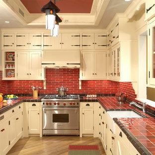 Источник вдохновения для домашнего уюта: п-образная, отдельная кухня в стиле рустика с техникой из нержавеющей стали, красным фартуком, столешницей из плитки, бежевыми фасадами, фасадами с утопленной филенкой, раковиной в стиле кантри, фартуком из керамической плитки, паркетным полом среднего тона, полуостровом и красной столешницей