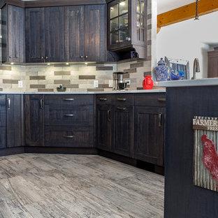 Idées déco pour une cuisine américaine campagne en U de taille moyenne avec un évier 2 bacs, un placard à porte shaker, des portes de placard en bois vieilli, un plan de travail en quartz, une crédence grise, une crédence en ardoise, un électroménager en acier inoxydable, une péninsule et un plan de travail blanc.