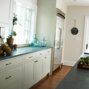 Transitional l-shaped kitchen photo in New York with a farmhouse sink, shaker cabinets, gray cabinets, limestone countertops, gray backsplash, subway tile backsplash and stainless steel appliances