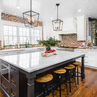 This is an example of a large traditional kitchen in DC Metro with a farmhouse sink, shaker cabinets, white cabinets, quartz benchtops, red splashback, brick splashback, stainless steel appliances, with island, white benchtop and medium hardwood floors.