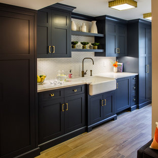 This is an example of a medium sized country kitchen in New York with a belfast sink, shaker cabinets, black cabinets, engineered stone countertops, white splashback, matchstick tiled splashback, porcelain flooring and brown floors.