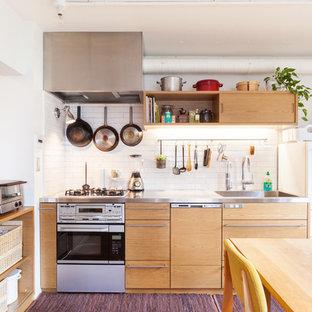 Inspiration för mellanstora industriella linjära kök med öppen planlösning, med en integrerad diskho, släta luckor, skåp i ljust trä, vitt stänkskydd, stänkskydd i tunnelbanekakel, vita vitvaror, bänkskiva i rostfritt stål och heltäckningsmatta