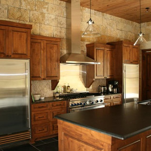 Mid-sized farmhouse eat-in kitchen inspiration - Eat-in kitchen - mid-sized cottage single-wall porcelain tile and black floor eat-in kitchen idea in Austin with an undermount sink, shaker cabinets, medium tone wood cabinets, solid surface countertops, beige backsplash, stone slab backsplash, stainless steel appliances and an island