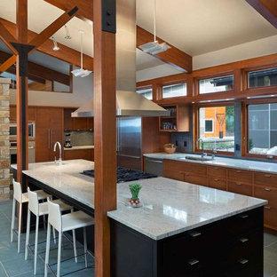 Foto de cocina moderna, grande, con fregadero bajoencimera, armarios con paneles lisos, puertas de armario de madera oscura, encimera de granito, salpicadero verde, salpicadero con mosaicos de azulejos, electrodomésticos de acero inoxidable, suelo de pizarra y una isla