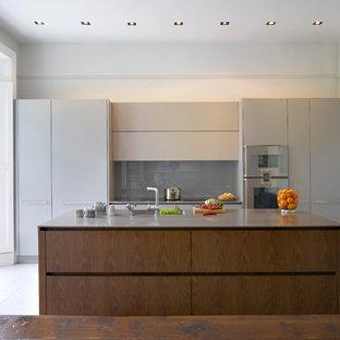 ロンドンの大きいコンテンポラリースタイルのおしゃれなキッチン (アンダーカウンターシンク、フラットパネル扉のキャビネット、ステンレスカウンター、グレーのキッチンパネル、ガラス板のキッチンパネル、シルバーの調理設備の) の写真