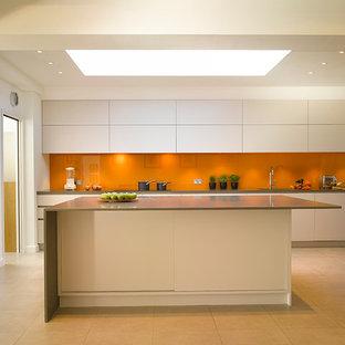 Offene, Große Moderne Küche mit Unterbauwaschbecken, flächenbündigen Schrankfronten, Mineralwerkstoff-Arbeitsplatte, Küchenrückwand in Orange, Glasrückwand, Küchengeräten aus Edelstahl, Kücheninsel und weißen Schränken in London