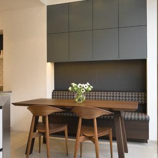 Cette image montre une grande cuisine américaine design avec un placard à porte plane et des portes de placard grises.