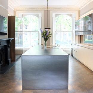 Offene, Zweizeilige, Große Moderne Küche mit Unterbauwaschbecken, flächenbündigen Schrankfronten, braunen Schränken, Edelstahl-Arbeitsplatte, Küchenrückwand in Metallic, Glasrückwand, Küchengeräten aus Edelstahl und Kücheninsel in London