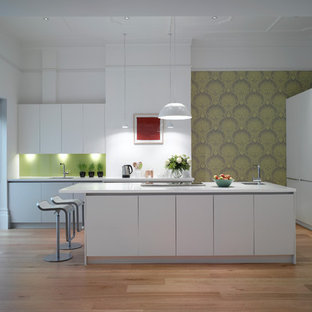 Design ideas for a large contemporary open plan kitchen in London with an undermount sink, flat-panel cabinets, white cabinets, solid surface benchtops, glass sheet splashback and with island.