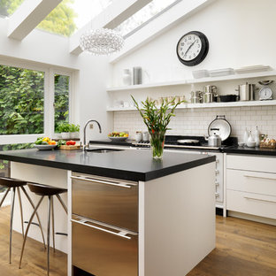 Large trendy kitchen photo in London with flat-panel cabinets, white cabinets, solid surface countertops and an undermount sink