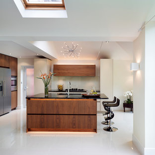 Photo of a large contemporary open plan kitchen in London with flat-panel cabinets, medium wood cabinets, granite worktops, an island, a submerged sink, beige splashback and stainless steel appliances.