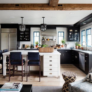 Mid-sized eclectic open concept kitchen photos - Mid-sized eclectic l-shaped light wood floor and brown floor open concept kitchen photo in New York with an undermount sink, black cabinets, quartz countertops, white backsplash, ceramic backsplash, stainless steel appliances and an island