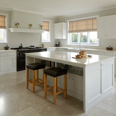Mid-sized elegant l-shaped limestone floor and beige floor kitchen photo in Hampshire with a farmhouse sink, shaker cabinets, white cabinets, quartzite countertops, black appliances, an island and white countertops