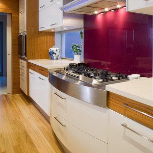 パースのアジアンスタイルのおしゃれなキッチン (アンダーカウンターシンク、フラットパネル扉のキャビネット、白いキャビネット、御影石カウンター、白いキッチンパネル、ガラス板のキッチンパネル、シルバーの調理設備の、淡色無垢フローリング) の写真