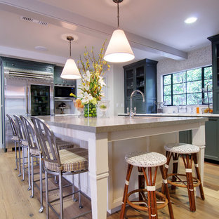 Large traditional kitchen designs - Example of a large classic l-shaped light wood floor kitchen design in Los Angeles with mosaic tile backsplash, stainless steel appliances, green cabinets, an island, recessed-panel cabinets and granite countertops
