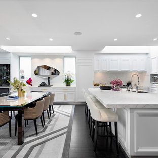This is an example of a contemporary l-shaped eat-in kitchen in Sydney with a double-bowl sink, recessed-panel cabinets, white cabinets, white splashback, stone slab splashback, dark hardwood floors, with island and white benchtop.