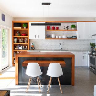 Moderne Küche in L-Form mit Waschbecken, offenen Schränken, hellbraunen Holzschränken, Küchenrückwand in Weiß, Rückwand aus Metrofliesen, Küchengeräten aus Edelstahl, Betonboden, Kücheninsel, grauem Boden und grauer Arbeitsplatte in Sonstige
