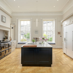 This is an example of a large transitional galley eat-in kitchen in Edinburgh with an integrated sink, shaker cabinets, blue cabinets, quartz benchtops, panelled appliances, light hardwood floors, with island, brown floor, grey benchtop, grey splashback and marble splashback.