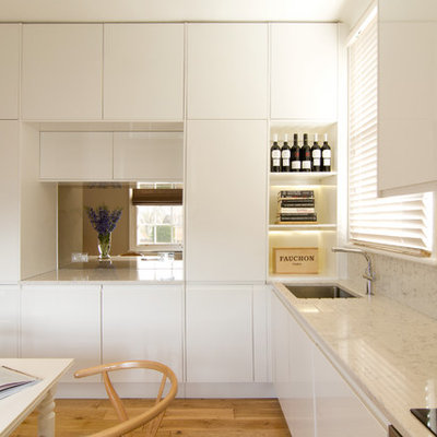 Eat-in kitchen - mid-sized contemporary l-shaped medium tone wood floor eat-in kitchen idea in London with a single-bowl sink, flat-panel cabinets, white cabinets, quartz countertops, stainless steel appliances and no island