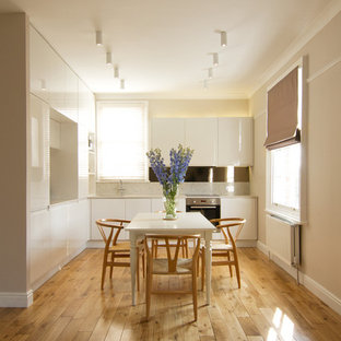 Inspiration for a medium sized contemporary l-shaped kitchen/diner in London with a single-bowl sink, flat-panel cabinets, white cabinets, engineered stone countertops, stainless steel appliances, medium hardwood flooring and no island.