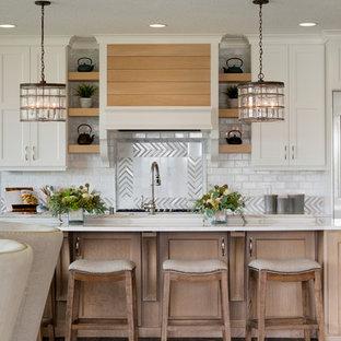 Immagine di una cucina chic con ante con riquadro incassato, ante bianche, paraspruzzi a effetto metallico, paraspruzzi con piastrelle di metallo, isola, pavimento marrone e top bianco