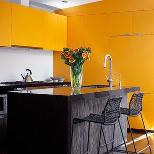 Diseño de cocina moderna con armarios con paneles lisos y puertas de armario naranjas