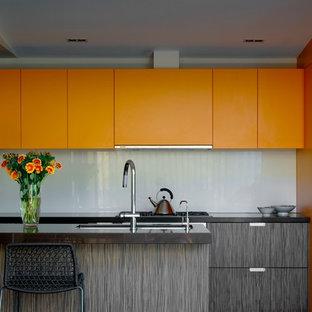 Idéer för funkis kök, med släta luckor, orange skåp och grått stänkskydd