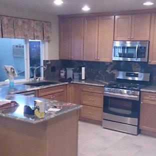 Foto på ett mellanstort funkis svart kök, med en undermonterad diskho, skåp i shakerstil, skåp i ljust trä, granitbänkskiva, svart stänkskydd, stänkskydd i sten, rostfria vitvaror, klinkergolv i porslin och beiget golv