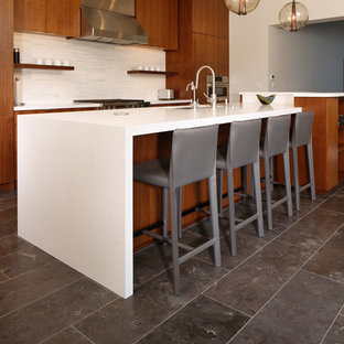 Inspiration for an expansive contemporary l-shaped eat-in kitchen in Los Angeles with an undermount sink, flat-panel cabinets, dark wood cabinets, quartz benchtops, white splashback, matchstick tile splashback, stainless steel appliances, marble floors, with island, blue floor and yellow benchtop.