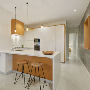 Photo of a midcentury u-shaped kitchen in Perth with a double-bowl sink, flat-panel cabinets, white cabinets, stainless steel appliances, concrete floors, a peninsula, grey floor and white benchtop.