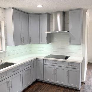 Klassisk inredning av ett mellanstort vit vitt kök, med en enkel diskho, skåp i shakerstil, grå skåp, bänkskiva i kvartsit, vitt stänkskydd, rostfria vitvaror, laminatgolv och brunt golv